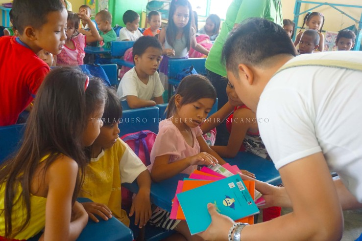 The author distributes notebooks to Grade 2 pupils. (photo by Ems Sicangco)
